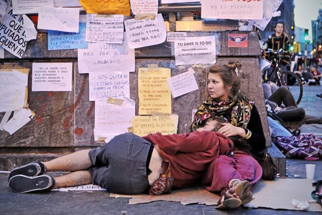 Dos activistas del 15-M, apoyados en una pared con carteles que...