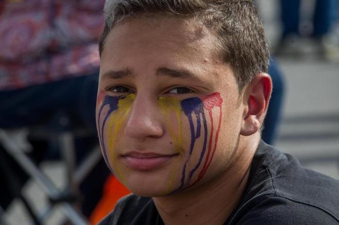Un manifestante simula lágrimas con pintura de los colores de la bandera nacional.