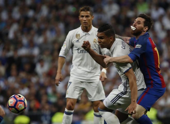 Cristiano observa la lucha por un balón entre Casemiro y Messi, en el pasado clásico.