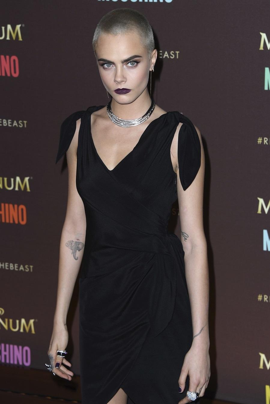 Lució un vestido negro asimétrico de Moschino con escote en v y...