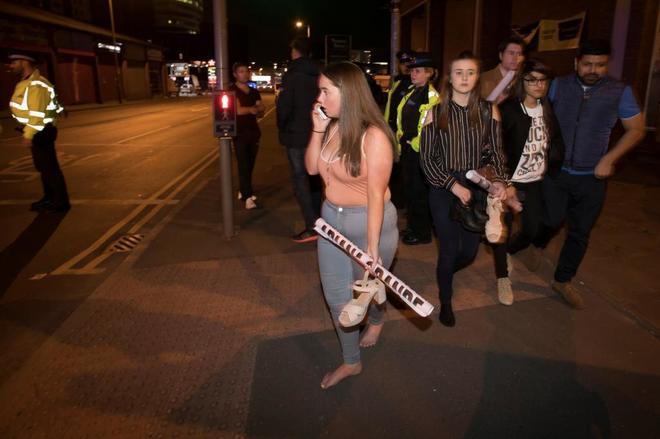 Varios asistentes al concierto de Ariana Grande abandonan el Manchester Arena tras el atentado.