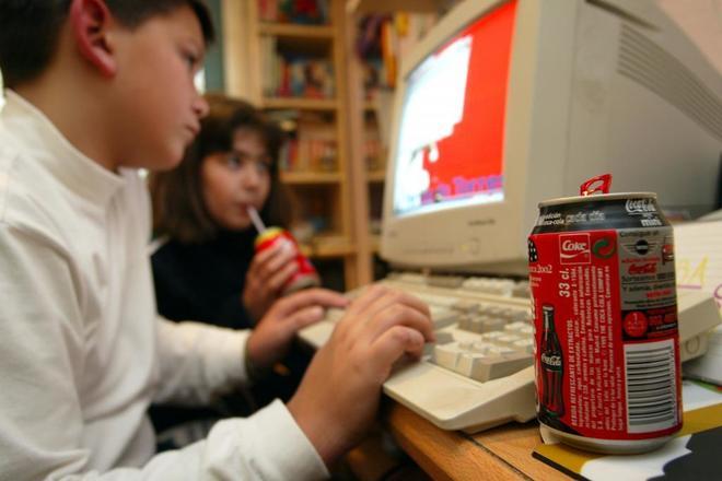 Niños consumiendo refrescos mientras trabajan frente al ordenador