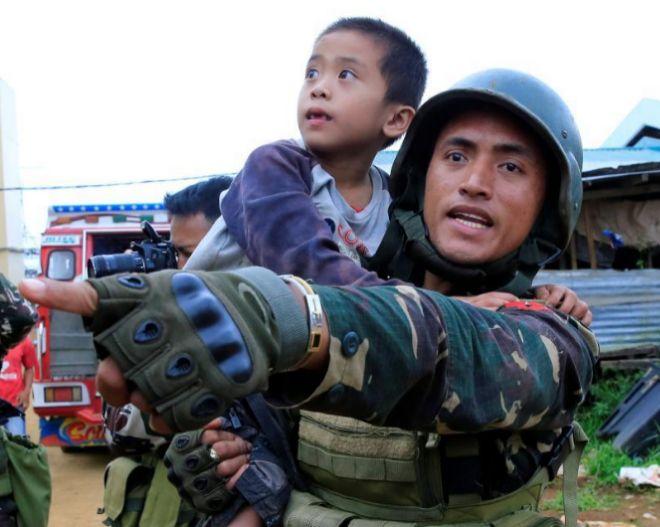 Un soldado filipino carga a un niño rescatado tras los combates con el grupo Maute en Papandayan (Marawi).