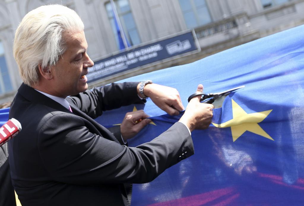 El líder de la ultraderecha holandesa Geert Wilders recorta una estrella de la bandera de la UE en Bruselas.