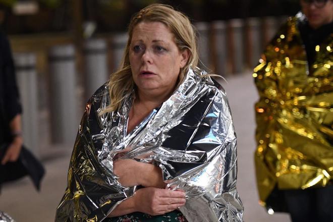 Una mujer envuelta en una manta abandona la escena.