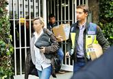 Agentes de la Policía portan documentos tras el registro del...