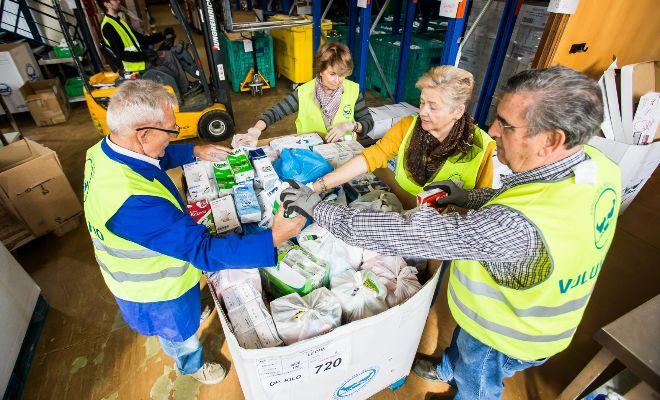 Varios voluntarios preparan palés de leche para ser repartidos a los más desfavorecidos en la Comunidad Valenciana.