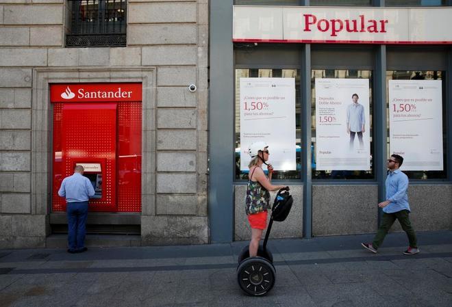 Un hombre hace uso de un cajero de Santander situado al lado de una sucursal de Banco Popular.