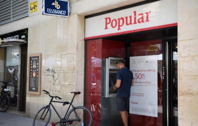 Un cliente saca dinero de un cajero de Banco Popular en Barcelona.