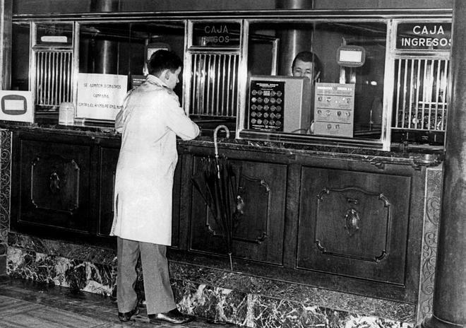Un cliente efectúa una operación en una sucursal del Banco Popular en Bilbao en 1972.