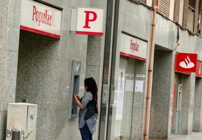 Una mujer hace uso de un cajero de Banco Popular cercano a una oficina de Banco Santander, en Barcelona.