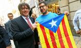 Puigdemont, posando ayer con un independentista y su 'estelada', en la...