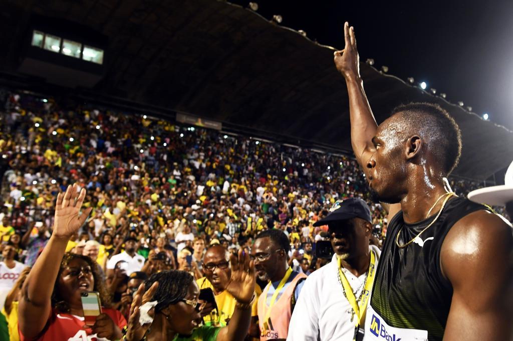 Usain Bolt saluda al público, que abarrotó el estadio de Kingston...