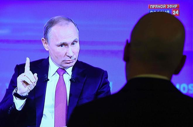 Un periodista observa al presidente ruso Vladimir Putin en su 'Línea directa' con los rusos.