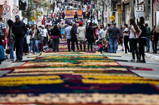 Personas caminando sobre el tradicional tapete gigante con motivo de la festividad del Corpus Christi este jueves.