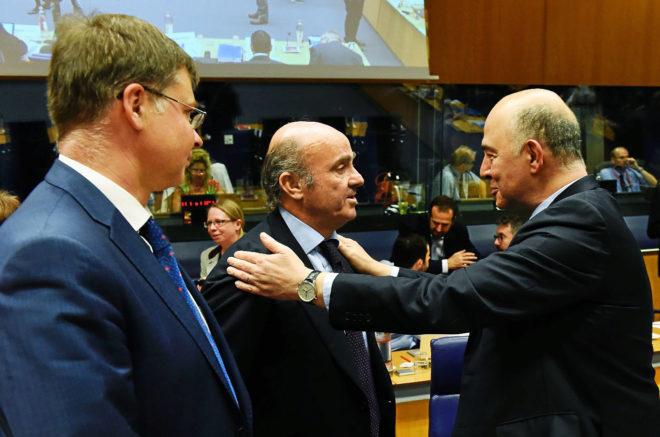 El ministro de Economía, Luis de Guindos, conversa con el comisario...