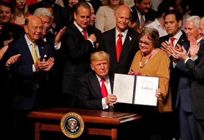 Donald Trump muestra el documento con su política sobre Cuba, rodeado de su Ejecutivo y de disidentes cubanos, en la Pequeña Habana.
