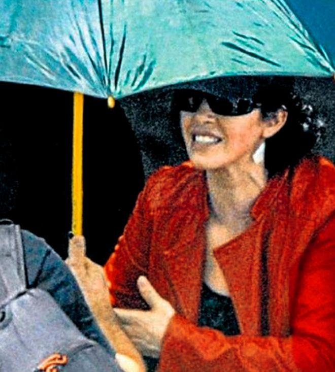 Idoia López Riaño intenta ocultarse bajo un paraguas al salir de prisión.