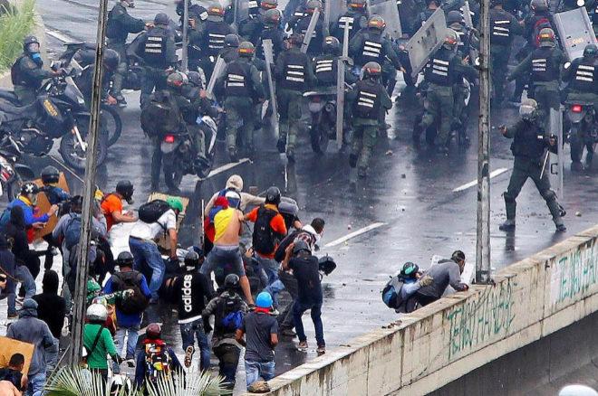 Un Policía venezolano apunta con un arma de fuego a los manifestantes.