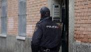 Un agente de la Policía Nacional custodia la entrada a una vivienda.