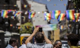 Un ciudadano toma ayer una fotografía de las banderolas arcoiris que...