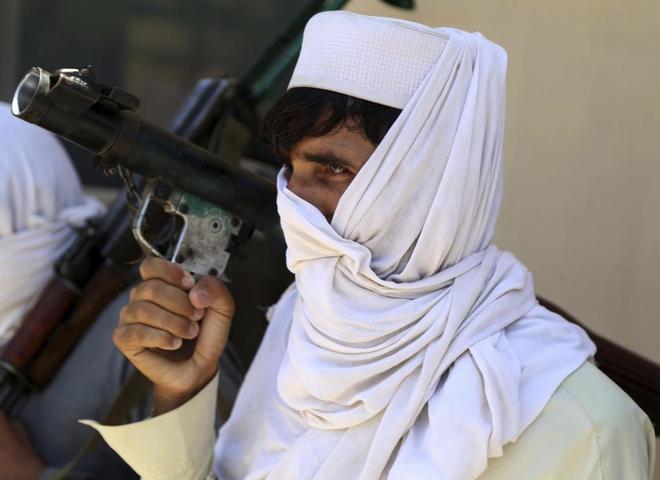 Un excombatiente talibán entrega su arma durante una ceremonia de reconciliación