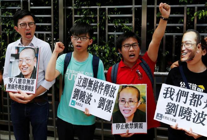 Joshua Wong (segundo por la derecha, rostro de la Revolución de los Paraguas), protesta por la situación de Xiaobo y de su mujer.