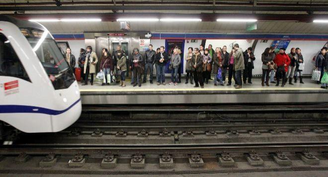 Pasajeros en un andén de la estación de Sol esperan la entrada de un tren.