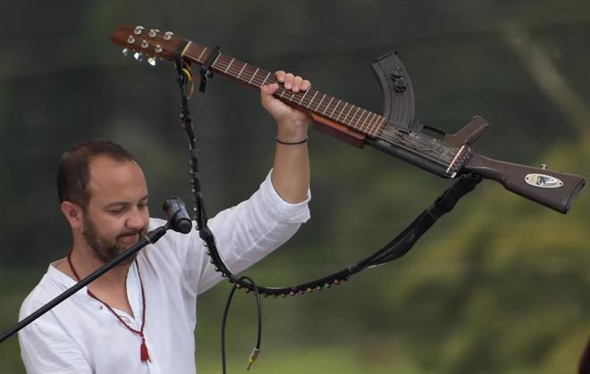 El músico y activista por los derechos humanos colombiano, César López, sostiene la 'escopetarra' mientras actúa al final del acto de la entrega de armas, este martes, en Colombia.