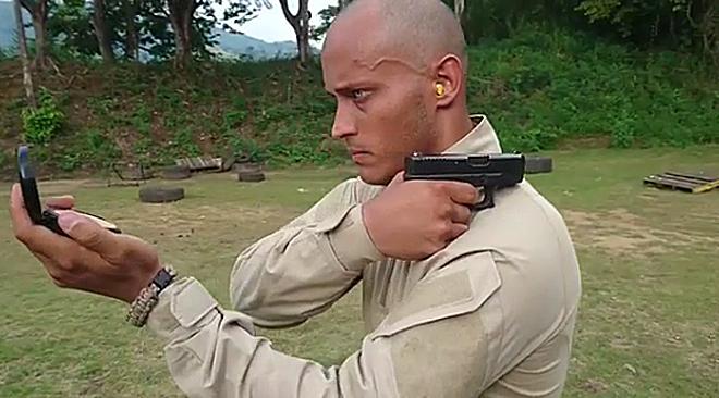 Óscar Pérez mira un espejo y apunta hacia atrás el objetivo de su pistola.