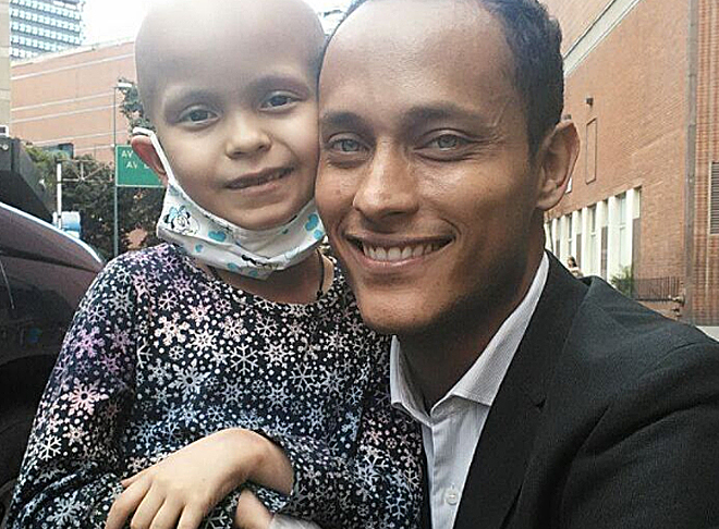 El policía posa con una niña enferma.
