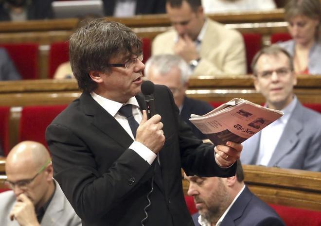 El presidente de la Generalitat, Carles Puigdemont, muestra un...