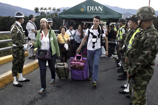 Gente con maletas pasando entre soldados por el puente internacional Simón Bolívar en Cúcuta, Colombia.