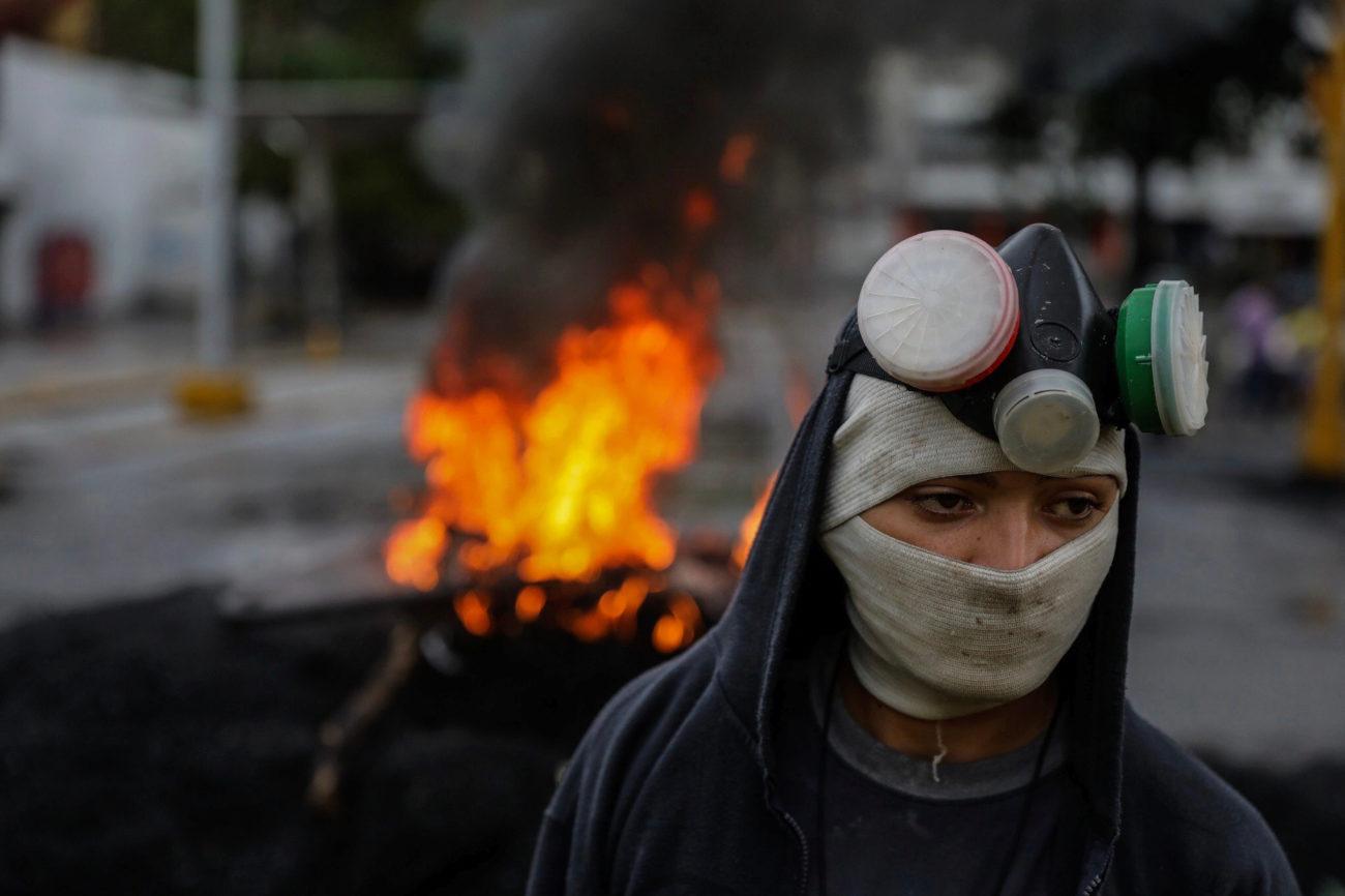 Una manifestante se protege como puede de los gases lacrimógenos que...