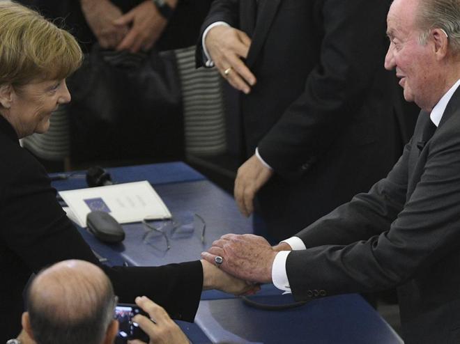 Merkel saluda al Rey Juan Carlos en el funeral.