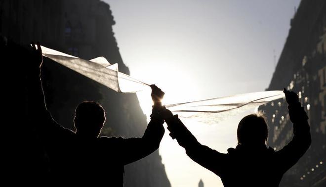 Ciudadanos con el pañuelo blanco que simboliza a las Madres de Plaza de Mayo, durante una protesta contra la reducción de la pena de un represor, en Buenos Aires.