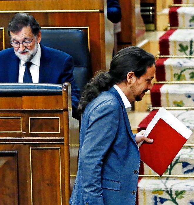 Pablo Iglesias pasa delante de Mariano Rajoy durante la sesión por la...