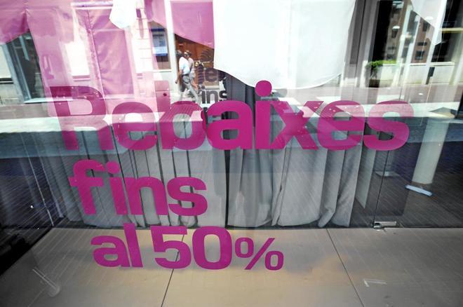 Un comercio anuncia rebajas con un letrero en catalán.