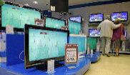 Una pareja, en una tienda de televisores.