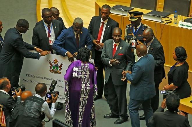 El presidente de Zimbabue, Robert Mugabe (centro), hace entrega de un cheque por valor de un millón de dólares  a la fundación de la Unión Africana.