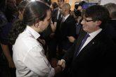 Pablo Iglesias y Carles Puigdemont se saludan en el acto en Madrid en...