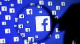 Una lupa sobre una pantalla con logotipos de Facebook.
