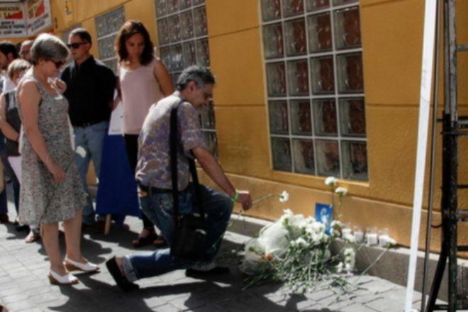 Un vecino coloca una flor en el altar a Miguel Ángel Blanco en Getafe frente a la mirada de la alcaldesa, Sara Hernández, de blanco en la foto.