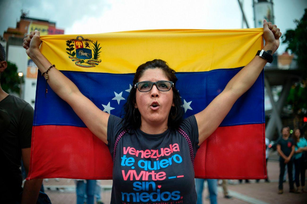Una mujer participa en la protesta a favor del plebiscito exhibiendo...