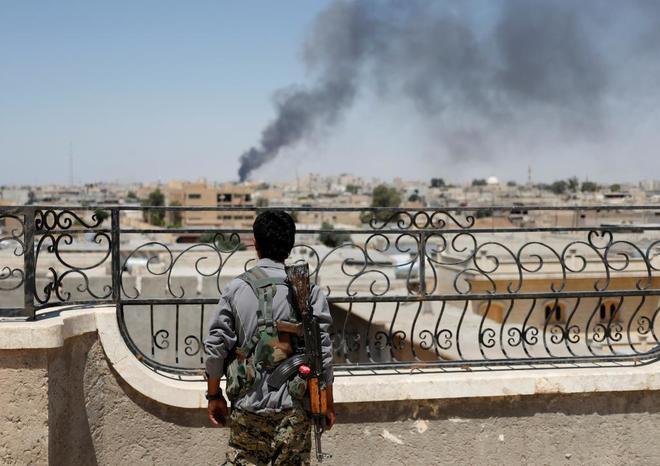 Un miliciano de las YPG kurdas observa una columna de humo en Raqqa.