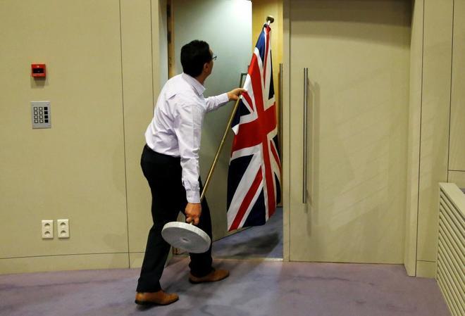 Un funcionario porta la bandera del Reino Unido antes de una conferencia de prensa entre los negociadores del Brexit británico y europeo, en Bruselas.