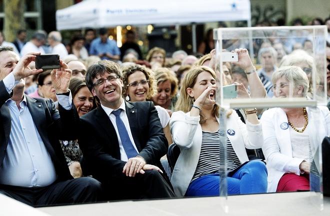 El presidente de Cataluña, Carles Puigdemont, junto a la dirigente...