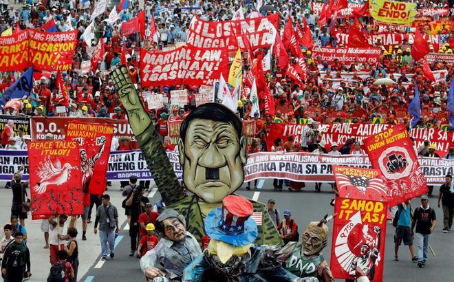 Manifestantes anti Duterte muestran una pancarta que caricaturiza al presidente durante una marcha hacia el parlamento filipino.