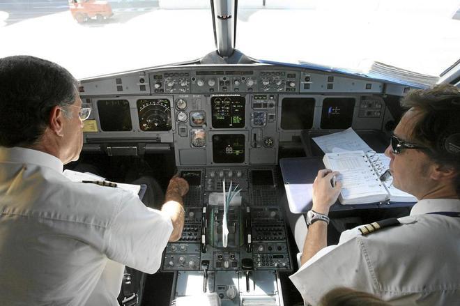 Pilotos en la cabina revisando instrumentos y plan de vuelo.