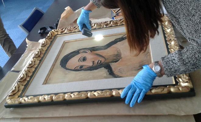 Una agente francesa de aduanas revisa 'Cabeza de mujer joven' tras su iniciación en Córcega. / EFE